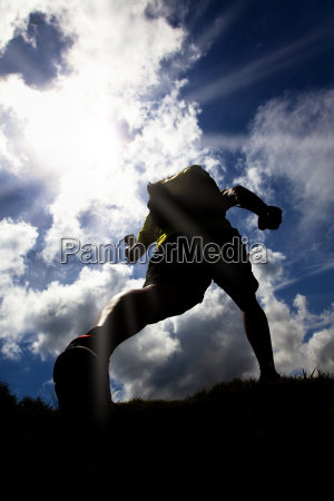 silhouette runner grass sunlight mountain sun
