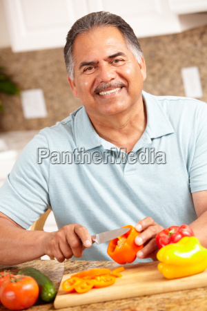 senior man chopping vegetables