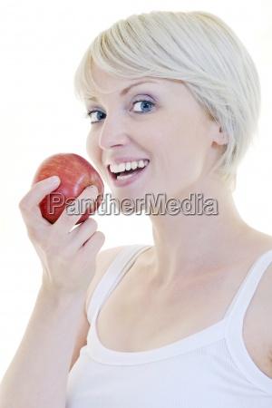 glueckliche junge frau essen gruenen apfel