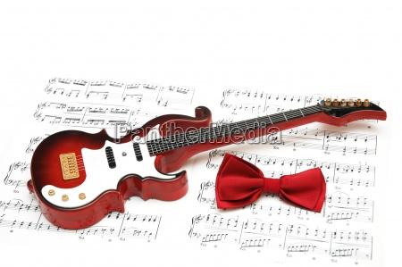 musiknotengitarre und fliege auf weissem