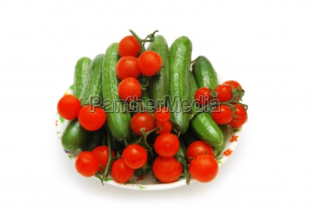 plate with cucumbers and tomatoes isolated