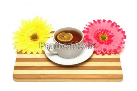 tasse tee auf holzbrett und blumen