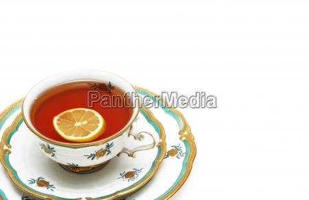 tee mit zitrone und untertassen isoliert