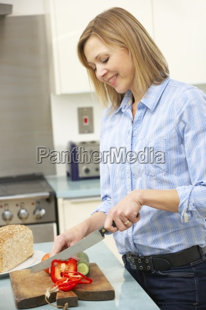 woman chopping vegetables in domestic kitchen