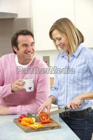 mature couple preparing meal in domestic