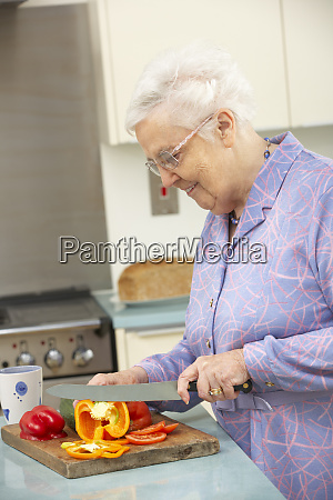 senior woman chopping vegetables in domestic
