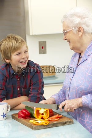 grandmother and grandson preparing food in