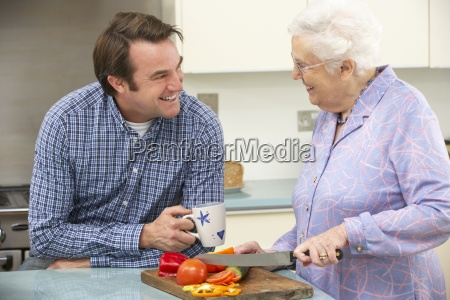 mother and adult son preparing meal
