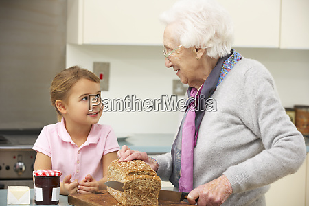 grandmother and granddaughter preparing food in