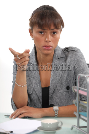 irritated businesswoman showing you the way