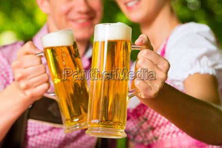 glueckliches paar mit bier im biergarten