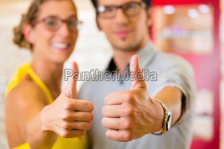 junges paar beim optiker kauft brille