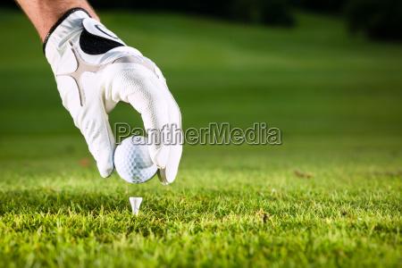 hand haelt golfball auf golfplatz mit