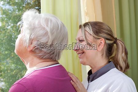 seniorin und pflegerin stehen am fenster