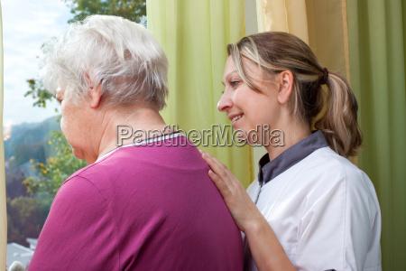 pflegerin und seniorin stehen am fenster