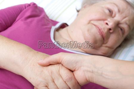 seniorin liegt im bett und begruesst