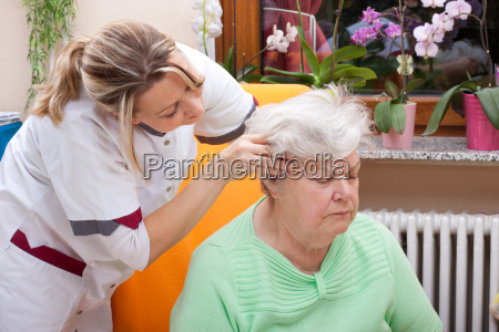 pflegerin massiert den kopf einer seniorin