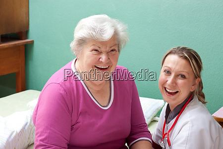patientin und aerztin lachen mit blick