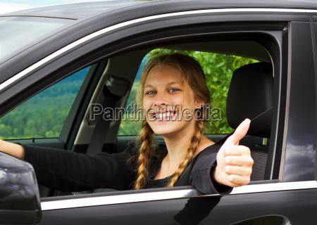 autofahrerin mit daumen nach oben