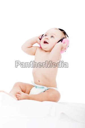 baby kleinkind mit rosa kopfhoerer als