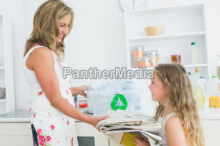 mother taking newspaper from daughte for