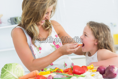 smiling mother feeding her daughter piece