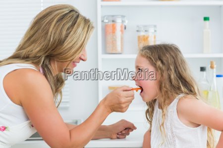 smiling mother feeding daughter carrot in