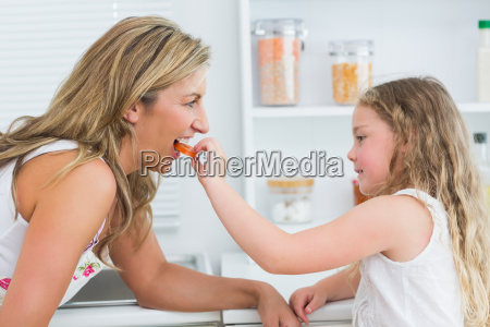 daughter feeding mother carrot in the