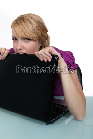 woman biting laptop
