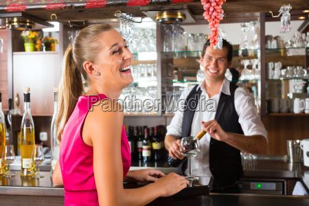 frau bestellt glas wein an bar