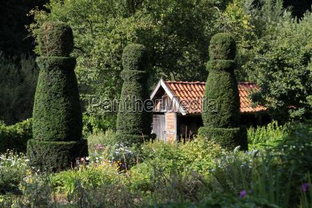 bauerngarten mit bienenstand und buchsbaumfiguren