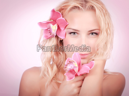 blond woman with pink orchid