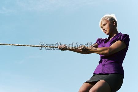 wettbewerbsfaehige geschaeftsfrau spielen tauziehen mit seil
