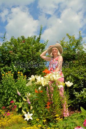 frau mit lilien im sommergarten
