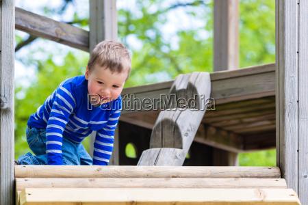 kleines kind spielt auf klettergeruest auf