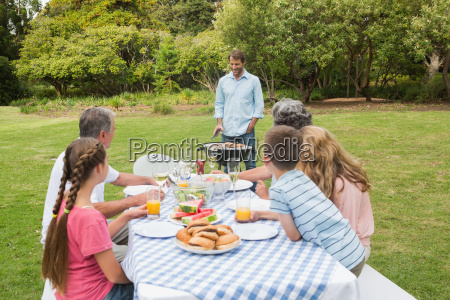 cheerful extended family watching father at