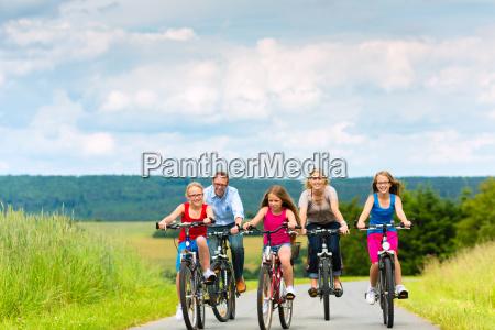 familie faehrt fahrrad im sommer in