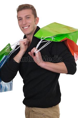 junger mann beim einkaufen mit einkaufstaschen
