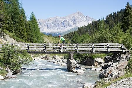 mountain biker crossing bridge
