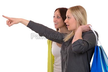 junge frau mit einkaufstaschen zeigt ihrer