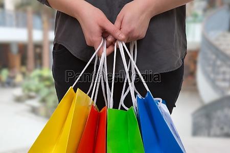 eine frau haelt bunte einkaufstaschen in