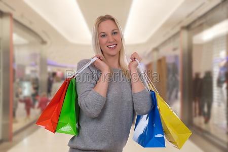 lachende blondine beim einkaufen in shopping