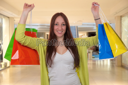 junge frau mit einkaufstaschen hat spass