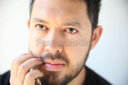 young man scratching his beard