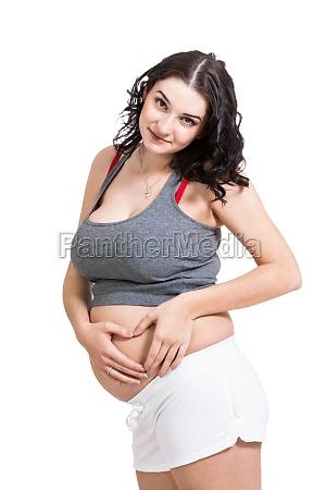 junge schwangere frau formt mit ihren