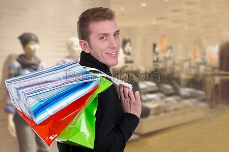lachender junger mann beim einkaufen mit