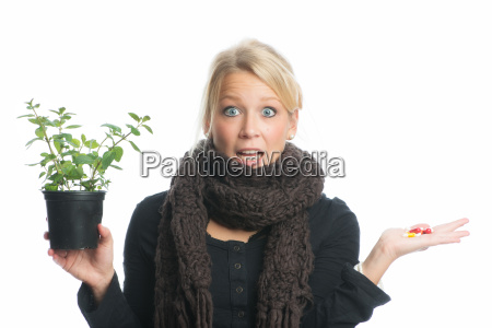frau mit heilpflanze und kapseln