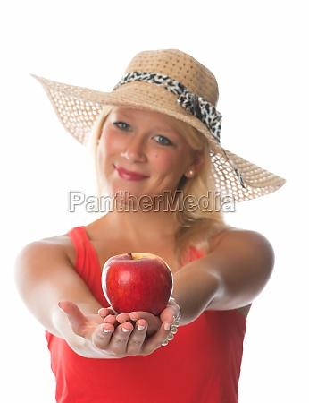 blonde frau haelt einen roten apfel
