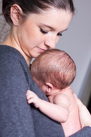 glueckliche junge mutter haelt ihr neugeborenes