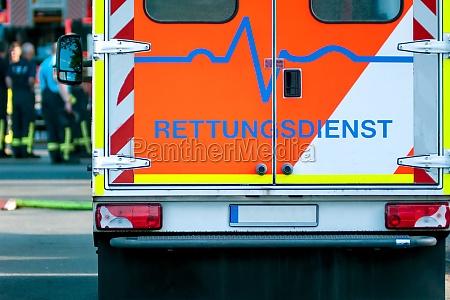 rettungsdienstwagen mit einsatzkraeften im hintergrund